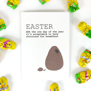 White card featuring an unwrapped broken easter egg with a bit of chocolate near it. To the top left of the card are the words EASTER AKA the one day of the year it's acceptable to have chocolate for breakfast' in black writing. Behind the card is a white background, and around the card you can see yellow chick chocolates.