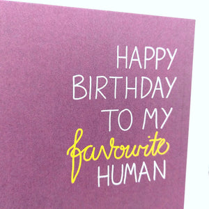 Rich purple card with the words 'HAPPY BIRTHDAY TO MY favourite HUMAN' in white capitals with the word favourite in yellow flowing handwriting. This image shows a close up of the writing. Behind the card is a white background.