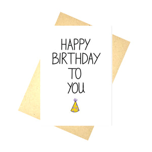 A white card with the words HAPPY BIRTHDAY TO YOU in black writing. Under the words is a little yellow party hat with lilac spots. Behind the card is a brown recycled paper envelope, behind which is a white background.