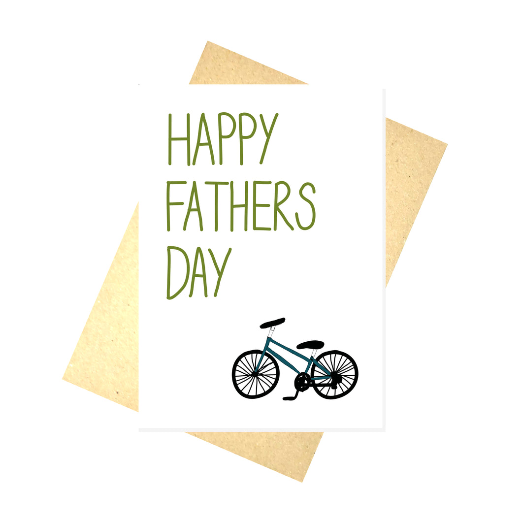 White card featuring the words HAPPY FATHERS DAY in a mossy green colour across the left. At the bottom right of the card is a bike with a blue frame. Behind the card is a brown envelope, behind which is a white background.