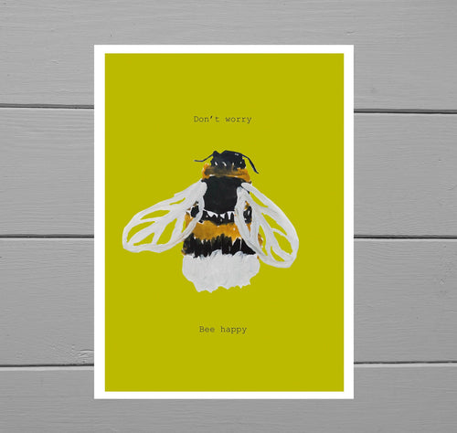 Close up of the Bee Happy Motivational Print featuring a warm yellow background and a hand drawn bee. Lying on a grey wooden plank background.