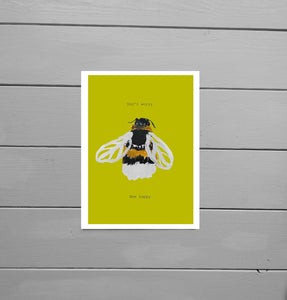 Bee Happy Motivational Print featuring a warm yellow background and a hand drawn bee. Lying on a grey wooden plank background - Duck Egg Designs Co