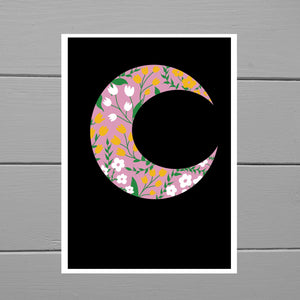 A pink crescent moon with white and mustard yellow tulip and daisy style flowers, alongside some green leaves and vines. Behind the moon is a black background with a white border. Behind the art print is a grey wooden plank background.