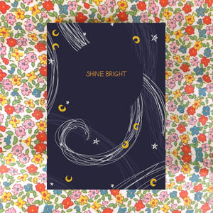 A dark blue card sits on a floral background. The card has the words SHINE BRIGHT across it in gold within a circle of dark blue, while around it are stars in white and moons in mustard yellow, as well as some curving lines in white and lighter blue inspired by the wind.