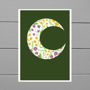 White crescent moon with pink and yellow tulip and daisy style flowers, and green leaves and vines. Behind the crescent moon is a forest green background with a white border. Behind the print is a grey wooden plant background.