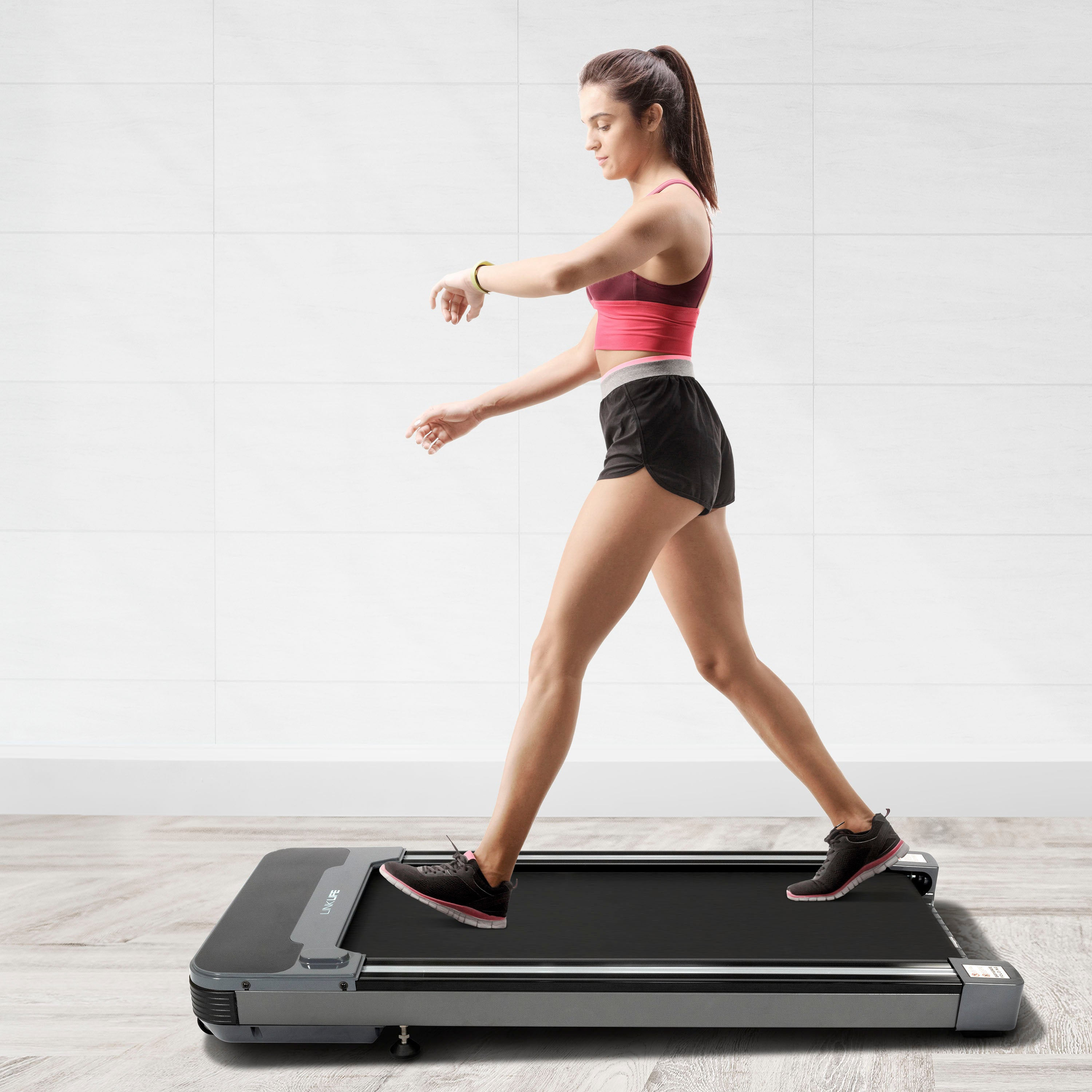 An image of a girl walking on the treadmill.