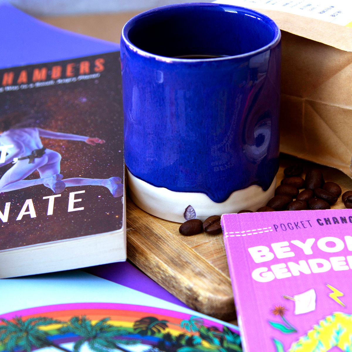Blue ceramic tumbler sits on wooden cutting board, surrounded by a book, greeting cards and coffee beans