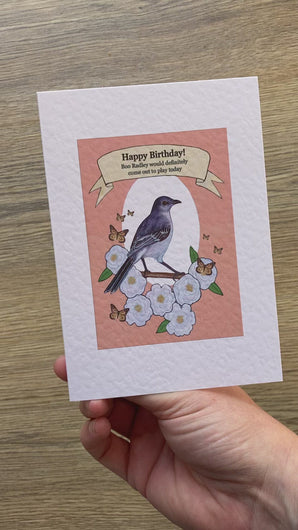 Video of a greetings card being opened and turned to show all sides. The card is inspired by the book 'To Kill a Mockingbird' by Harper Lee. It has an image of a mockingbird on the front and the words 'Happy Birthday! Boo Radley would definitely come out to play today.'