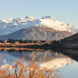 A wide shot of a New Zealand mountain and lake with a blue sky