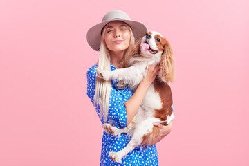 Girl in wide sun hat holding brown and white dog, pink background