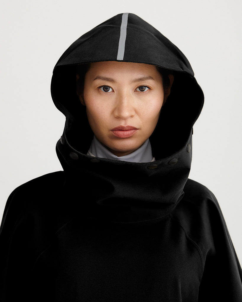 Close up of hood of black, waterproof, breathable, technical, sustainable and packable raincoat poncho suitable for cycling