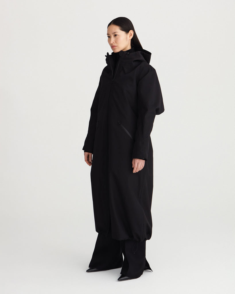 long, black, waterproof, breathable, technical and sustainable winter warm raincoat with recycled, detachable liner.
