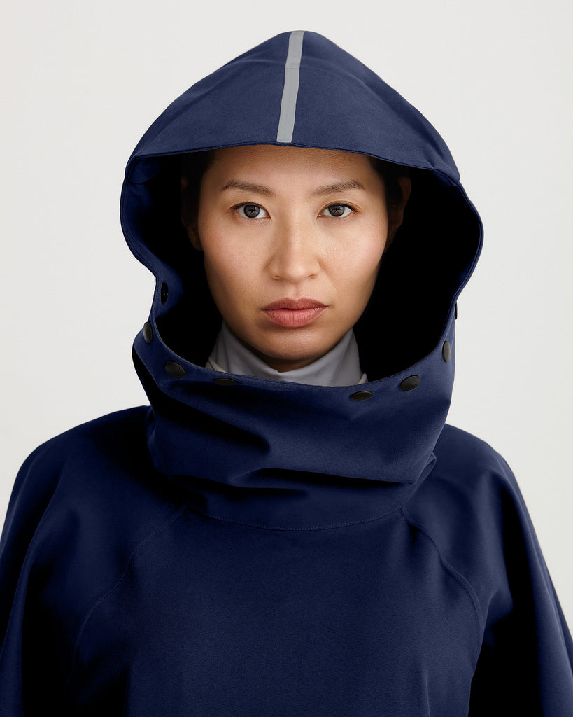 Close up of hood of navy blue, waterproof, breathable, technical, sustainable and packable raincoat poncho suitable for cycling