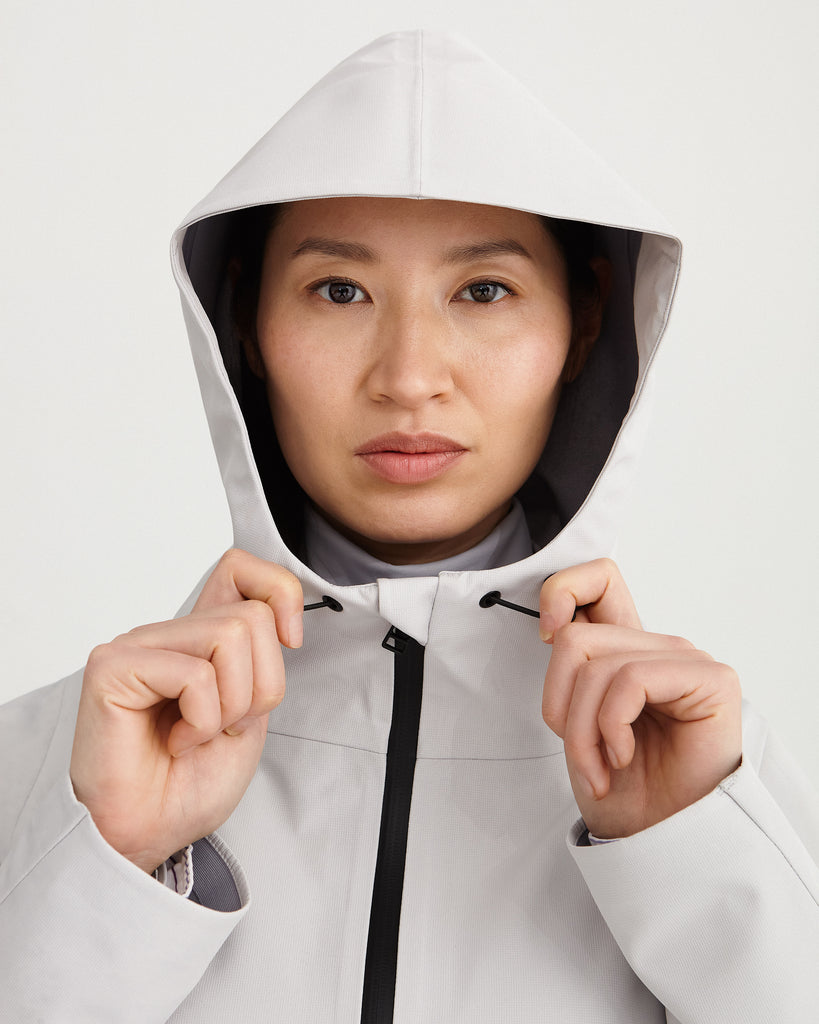 a face close up of midlength, grey, waterproof, breathable, sustainable and technical raincoat from recycled materials with hood.