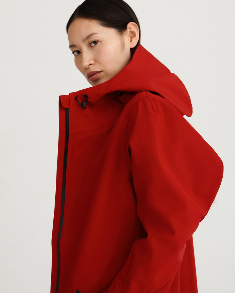 a side close up of midlength, red, waterproof, breathable, sustainable and technical raincoat from recycled materials with hood.