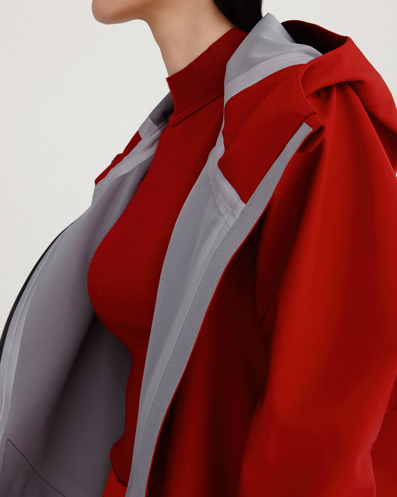 close up of sealed seams from midlength, red, waterproof, breathable, sustainable and technical raincoat from recycled materials with hood.