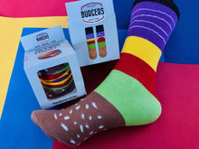 Load image into Gallery viewer, The socks are packed to actually look like a hamburger with all the fixings. Food socks that make a creative gift from Pomelo Socks. Back and front of Burger packaging is shown.