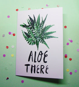 "Greeting card depicting a watercolour illustration of a green aloe vera plant against a white background. There is inky black hand lettering beneath the aloe which reads ""aloe there""."