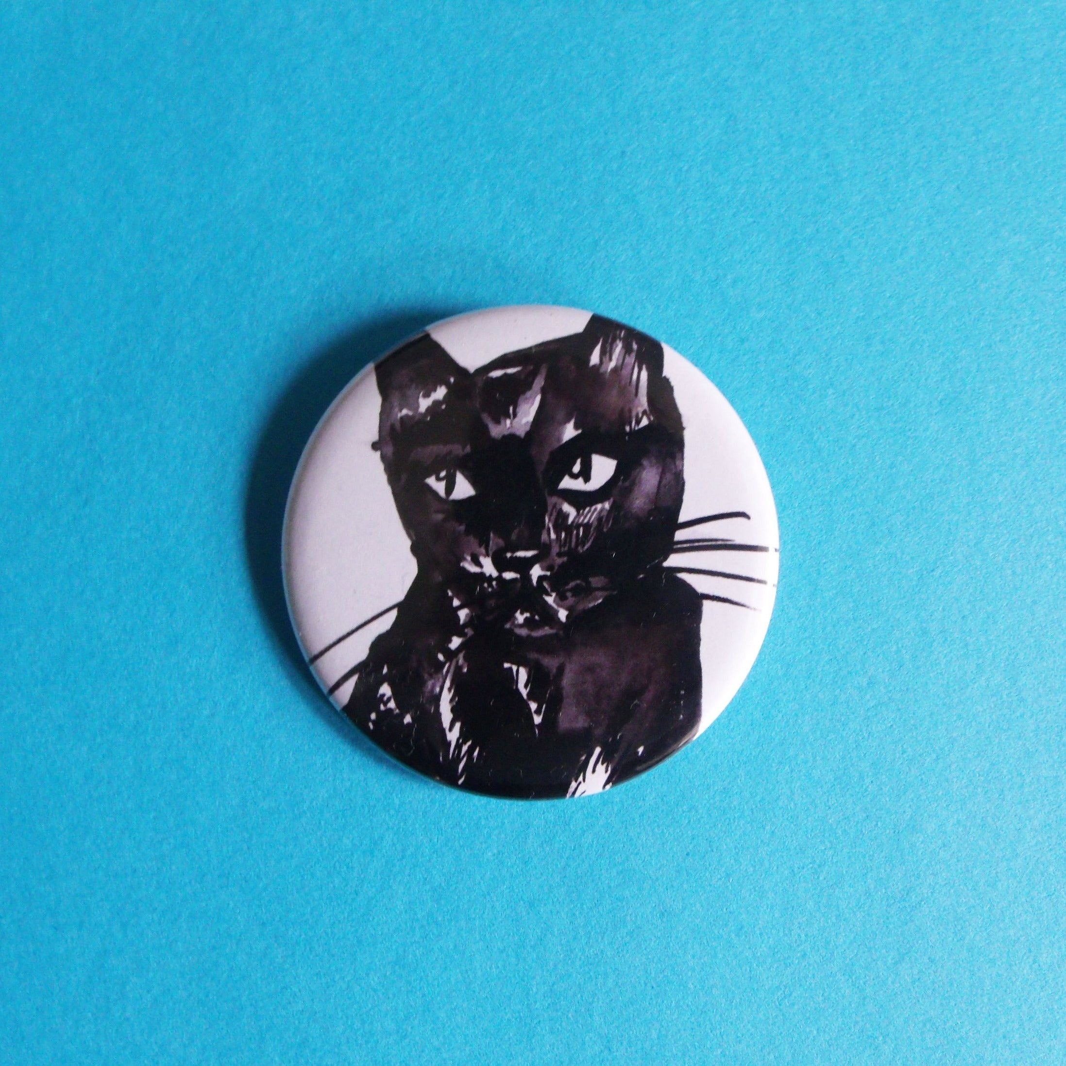 Large button badge. It features an ink illustration of a black cat against a white background.