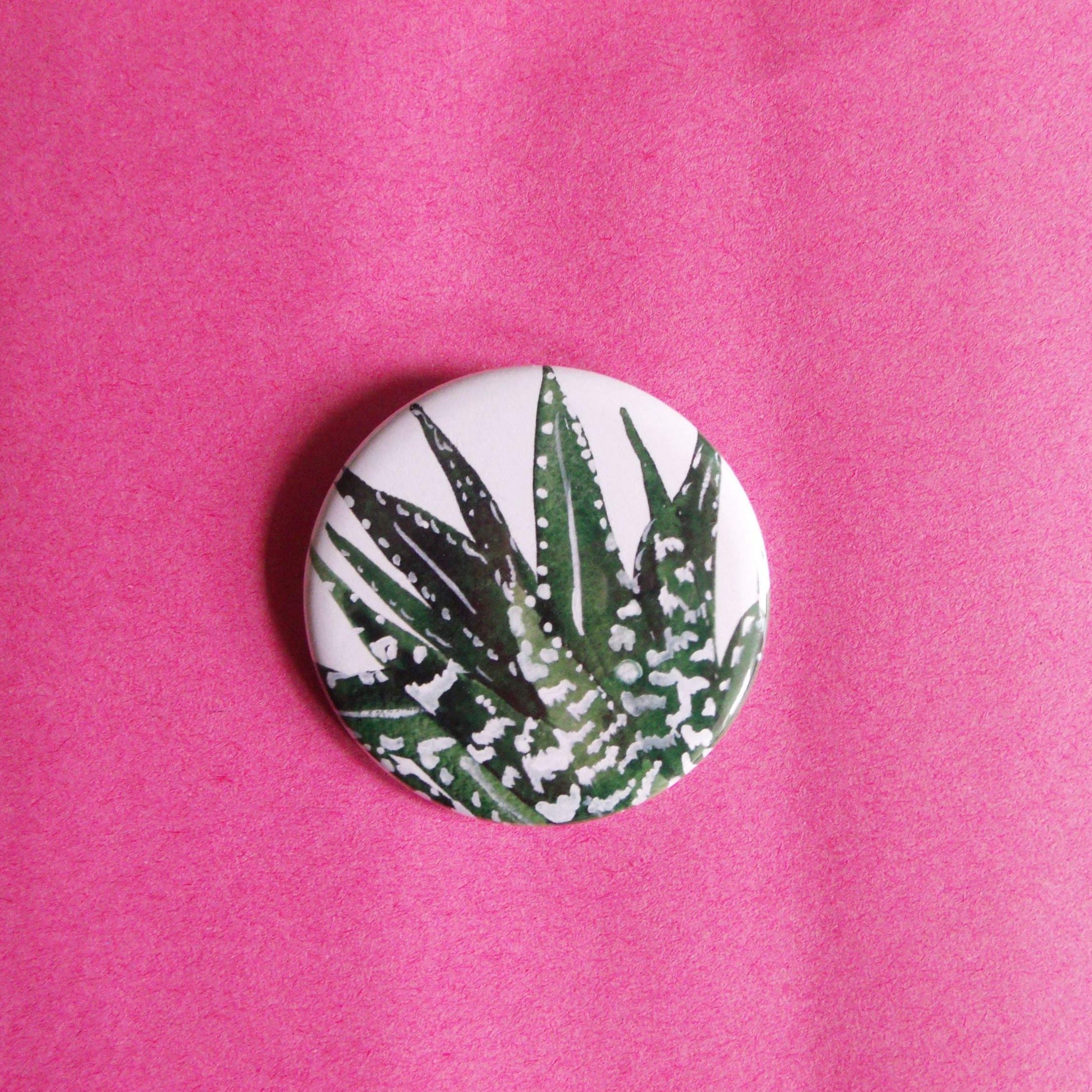 circular button badge with an illustration of an aloe vera plant on it.