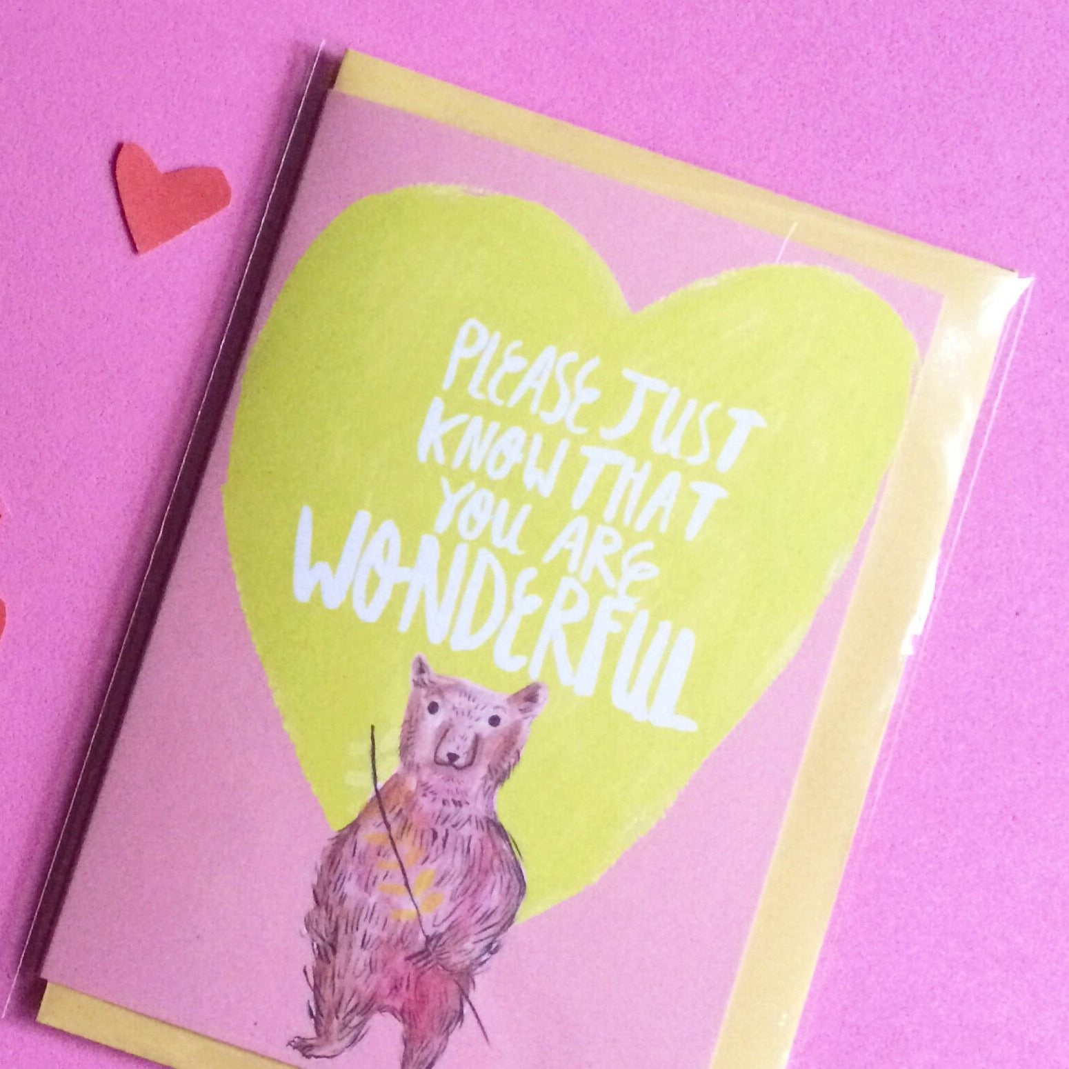 "A6 card with a yellow envelope. It features a watercolour and ink illustration of a cute brown bear holding a twig with yellow leaves. Above the bear is a yellow heart with white lettering that reads ""PLEASE JUST KNOW THAT YOU ARE WONDERFUL"". The background of the artwork is pink."