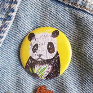 Image of a large circular button badge being held up against a green wall. The badge depicts an original gouache paint illustration of a cute panda with a yellow background.