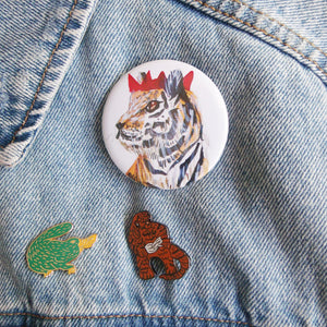Large button badge. It features a watercolour illustration of a tiger wearing a red party hat against a white background.
