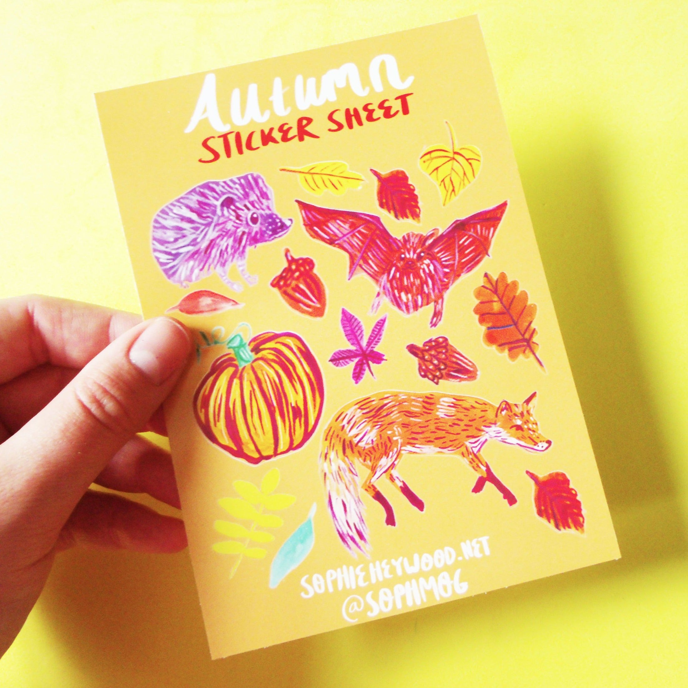 a6 sticker sheet. the sheet is orange and includes a hedgehog, pumpkin, bat, fox, acorns and leaves.