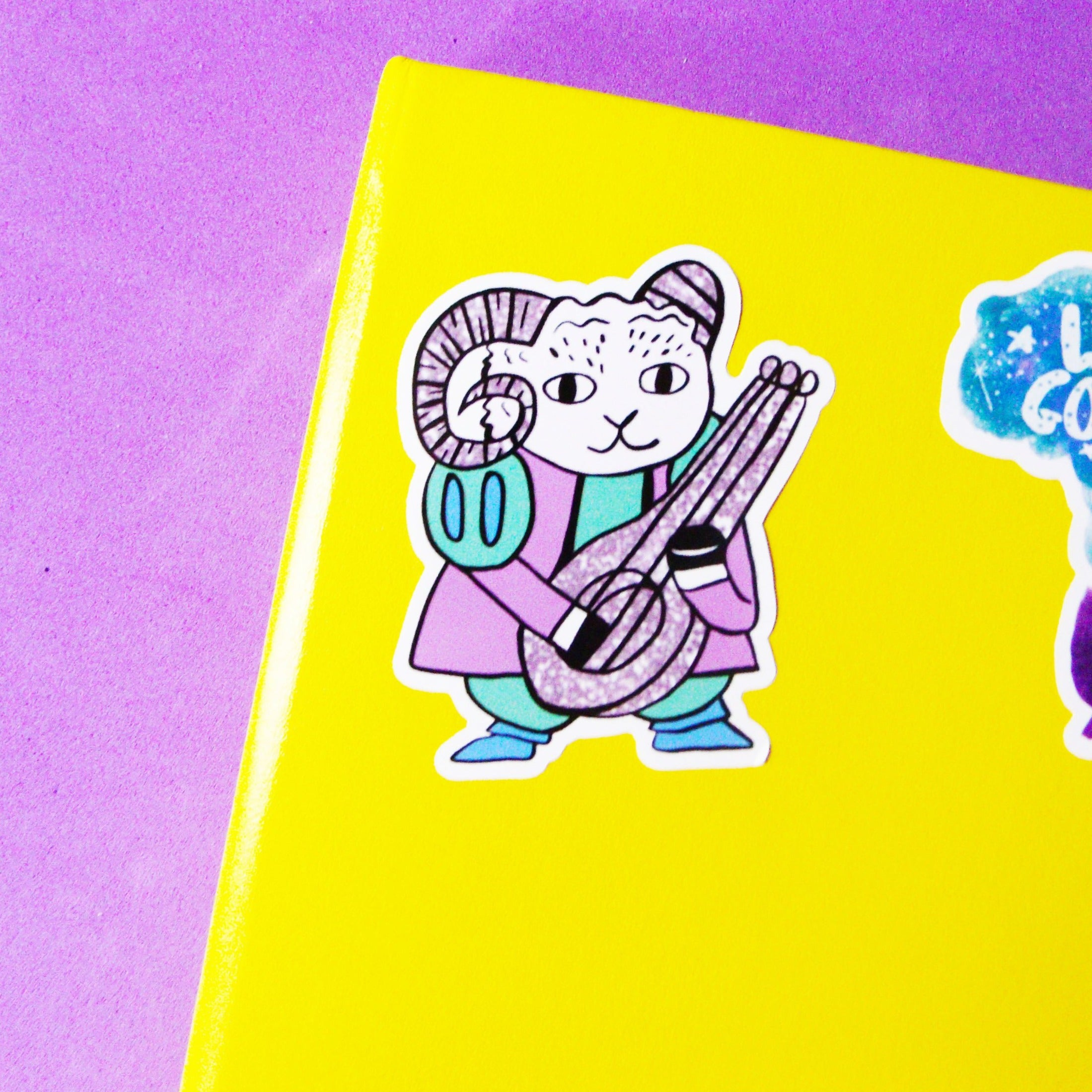 small vinyl sticker featuring a cute illustration of a goat dressed as a bard. he's holding a lute and wearing a green and purple outfit.