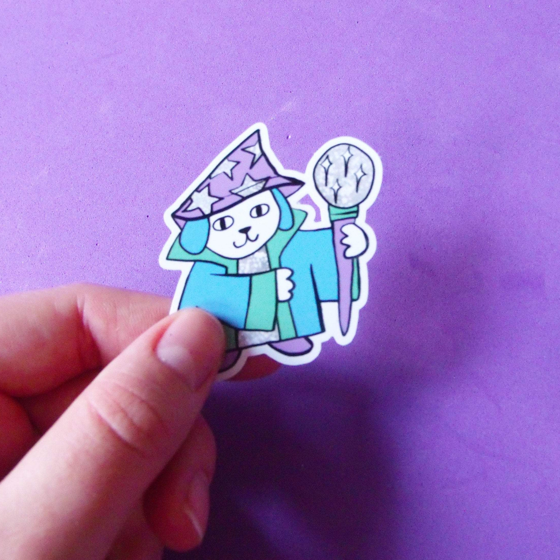 Sticker placed onto the corner of a yellow notebook. The sticker depicts an illustrated dog. He's a cute little wizard, wearing a robe, a star print hat and holding a staff.