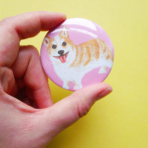 Hand holding a large circular button badge against a yellow background. The badge depicting a digital illustration of a cute corgi dog sticking its tongue out against a pink background.