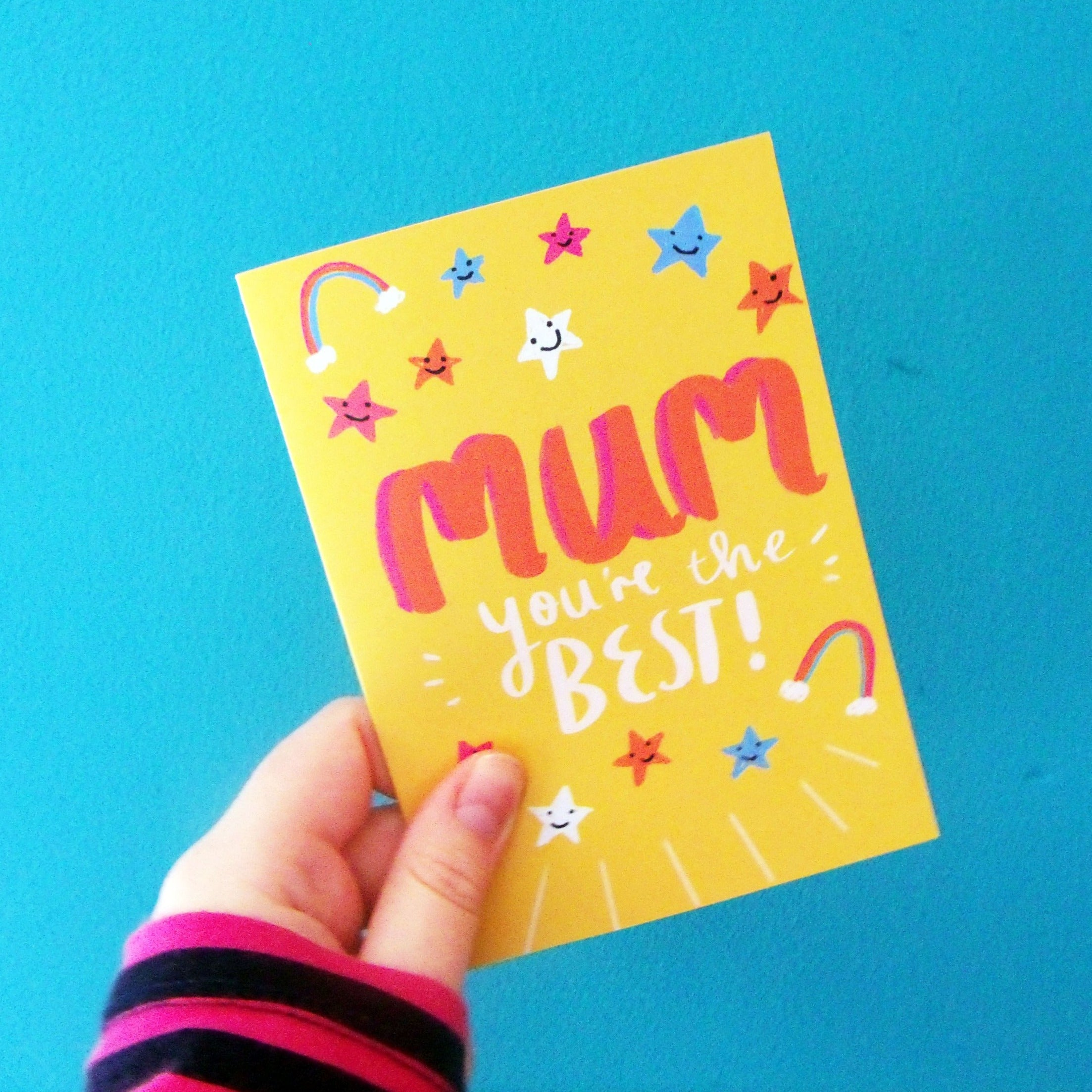"Image of an A6 greeting card against a pink and yellow background. The card depicts a digital illustration of a hand lettered quote which reads ""mum you're the best!"" there is a bright yellow background and cute little details such as rainbows and stars with smiley faces."