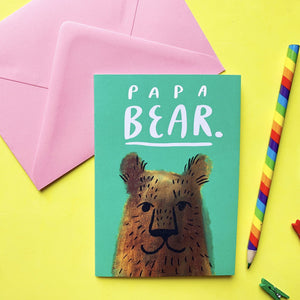 "Hand holding an A6 greeting card with a pink envelope. It features a digital illustration a cute brown bear smiling. There is lettering above that reads ""PAPA BEAR"" in white. The illustration is against a green background."