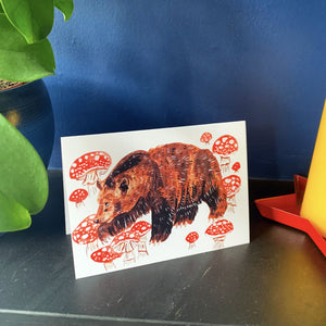 A6 greeting card with an orange envelope. It features a gouache illustration of a brown bear surrounded by red toadstools against a white background.