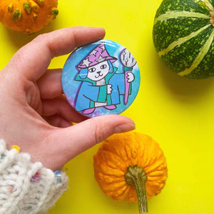 Image of a large button badge. It features a cute illustration of a wizard dog wearing a magical robe and hand, he's holding a staff.