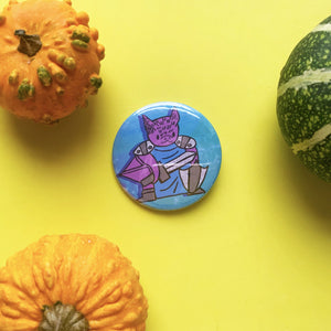 Hand holding a large button badge. It features an illustration of a cute bat knight. She has purple skin and is wearing a blue tunic with metal shoulder armour. She's holding a sword and a shield.