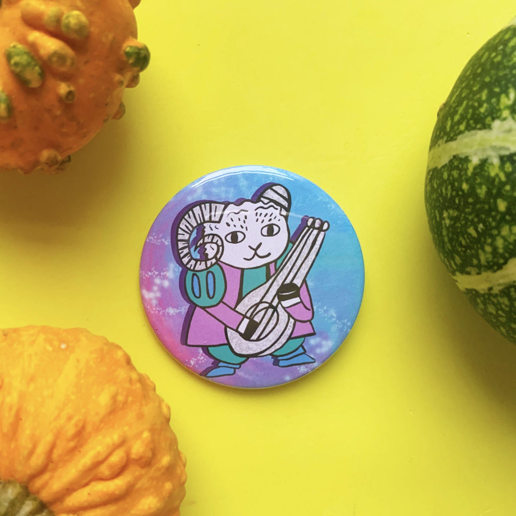 large circular button badge. it features a cute illustration of a goat dressed as a bard. he's holding a lute and is wearing a green and purple outfit. he's stood against a celestial star background.