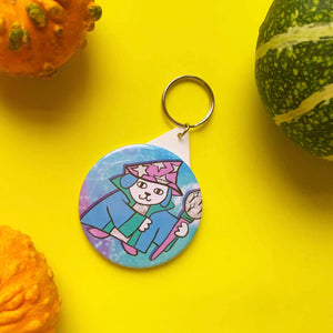 circular keyring featuring a cute illustration of a wizard dog. he's holding a staff, is wearing a cloak and has a hat with stars in it. he's stood against a celestial star background.