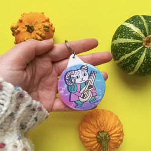 circular keyring featuring a cute illustration of a goat dress of a bard. he's holding a lute and wearing a green and purple outfit, stood against a celestial star background.