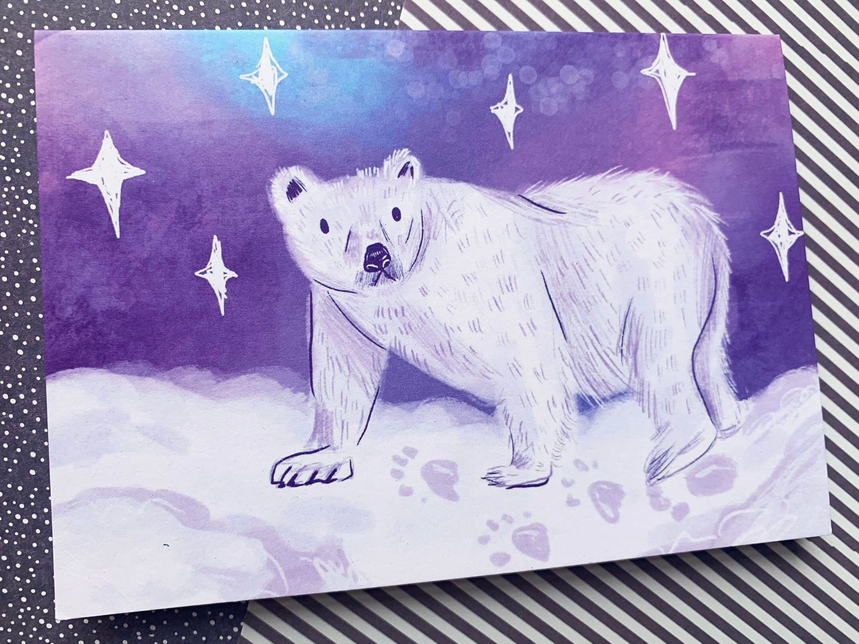 A6 greeting card. It features a digital illustration of a white polar bear walking along some snow. There is a celestial starry sky in the background.