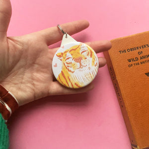 Hand holding a circular keyring. It features a cute digital illustration of a smiling chonky tiger against a white background.