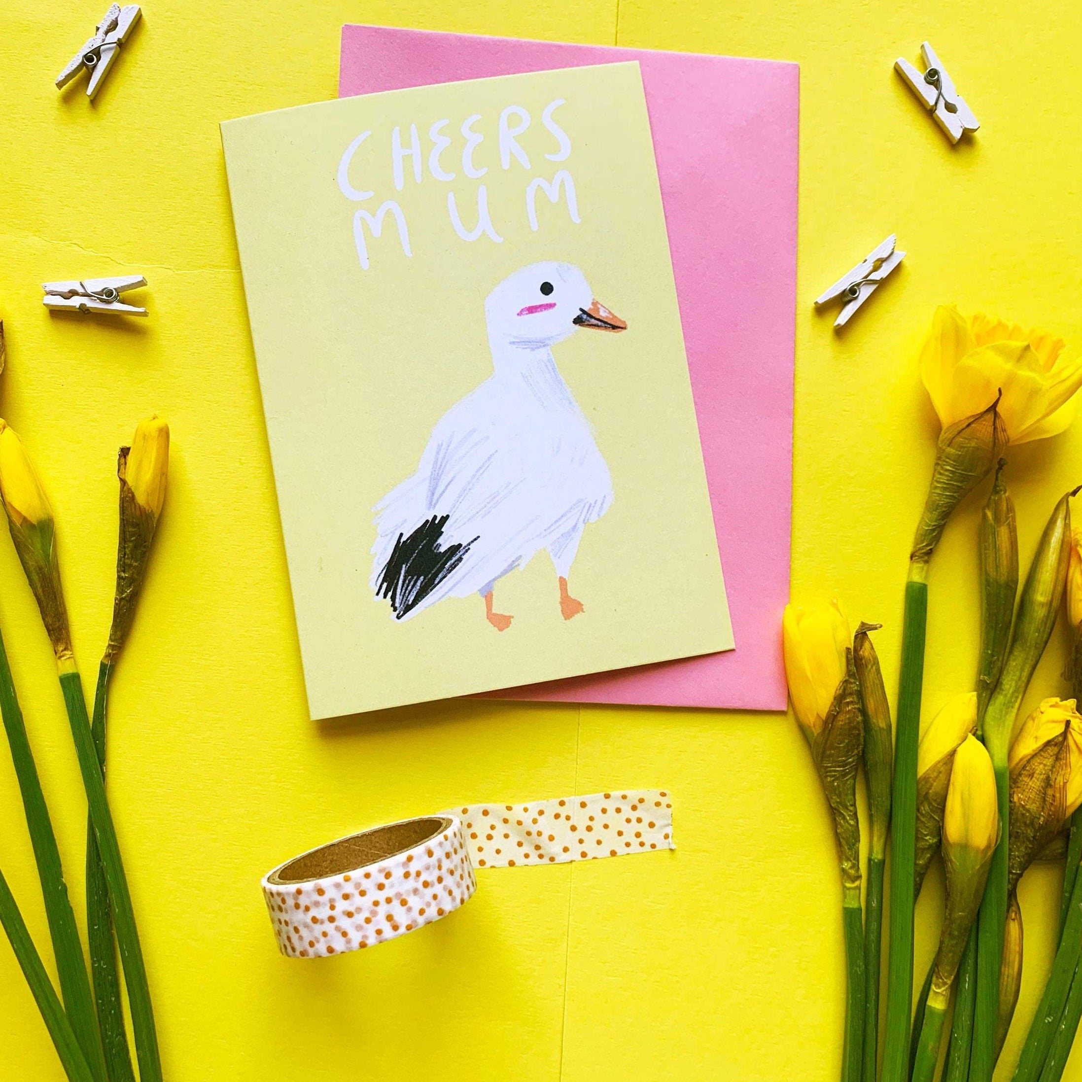 "A6 greeting card. It features a digital illustration of a white goose against a yellow background. It has a quote above the goose that reads ""CHEERS MUM"". The card is pictured with a pink envelope."