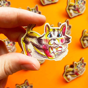 Hand holding a wooden pin. It features an illustration of a retro style kitsch kitten cat.
