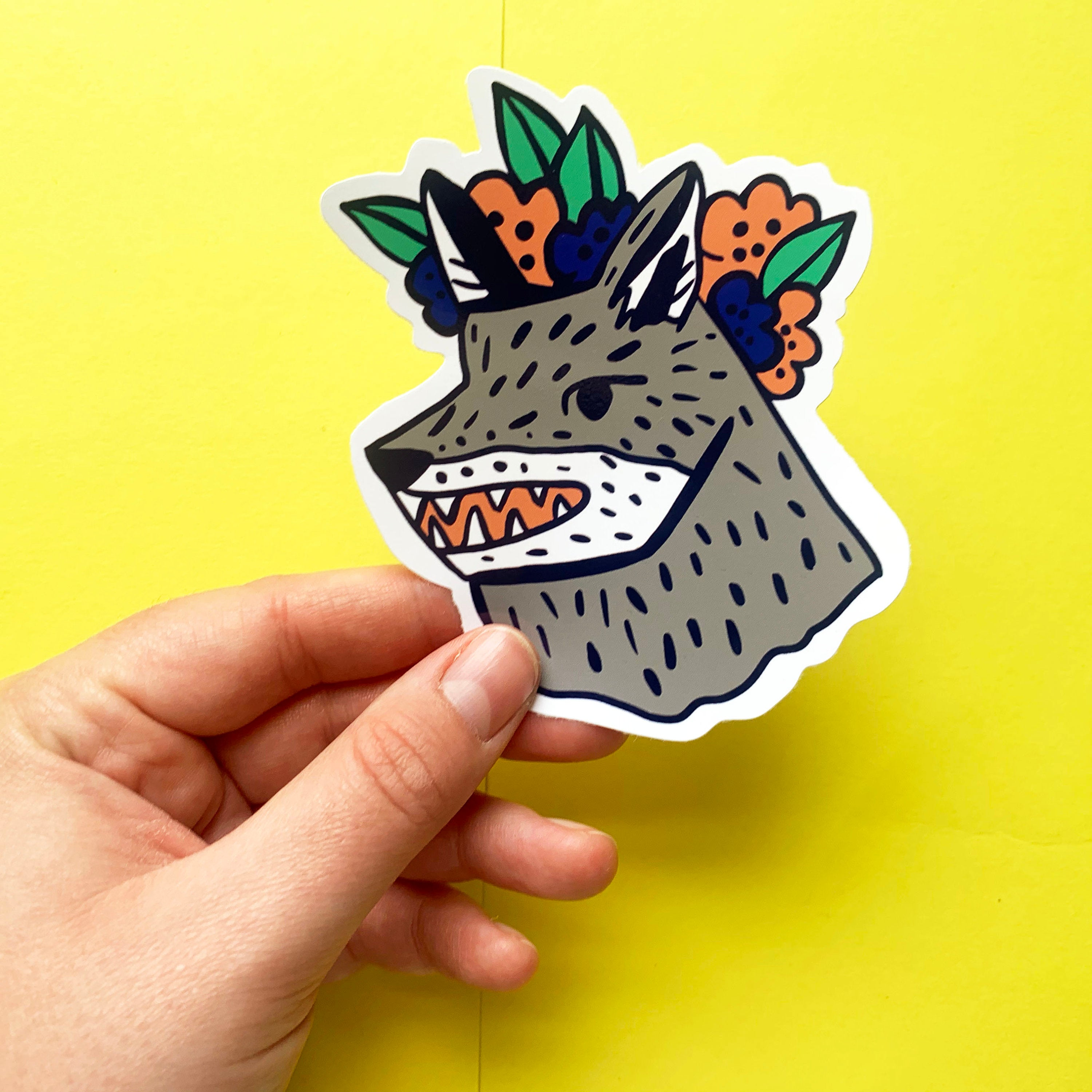 Hand holding a large vinyl sticker. It features an illustration of a grey wolf wearing a flower crown.