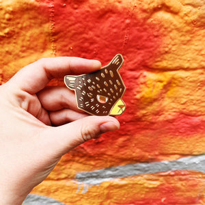 Hand holding a large enamel pin. It's shaped like a bear with a grumpy face. It has brown, yellow and white enamel with gold plating.