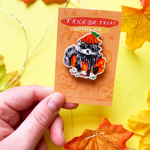 "Image of a hand holding a wooden pin affixed to recycled backing card against a yellow background. The wooden pin depicts an original gouache paint illustration of a cute stylised raccoon dressed in a pumpkin halloween outfit. The backing card is orange and there is hand lettering which reads ""trick or treat wooden pin""."