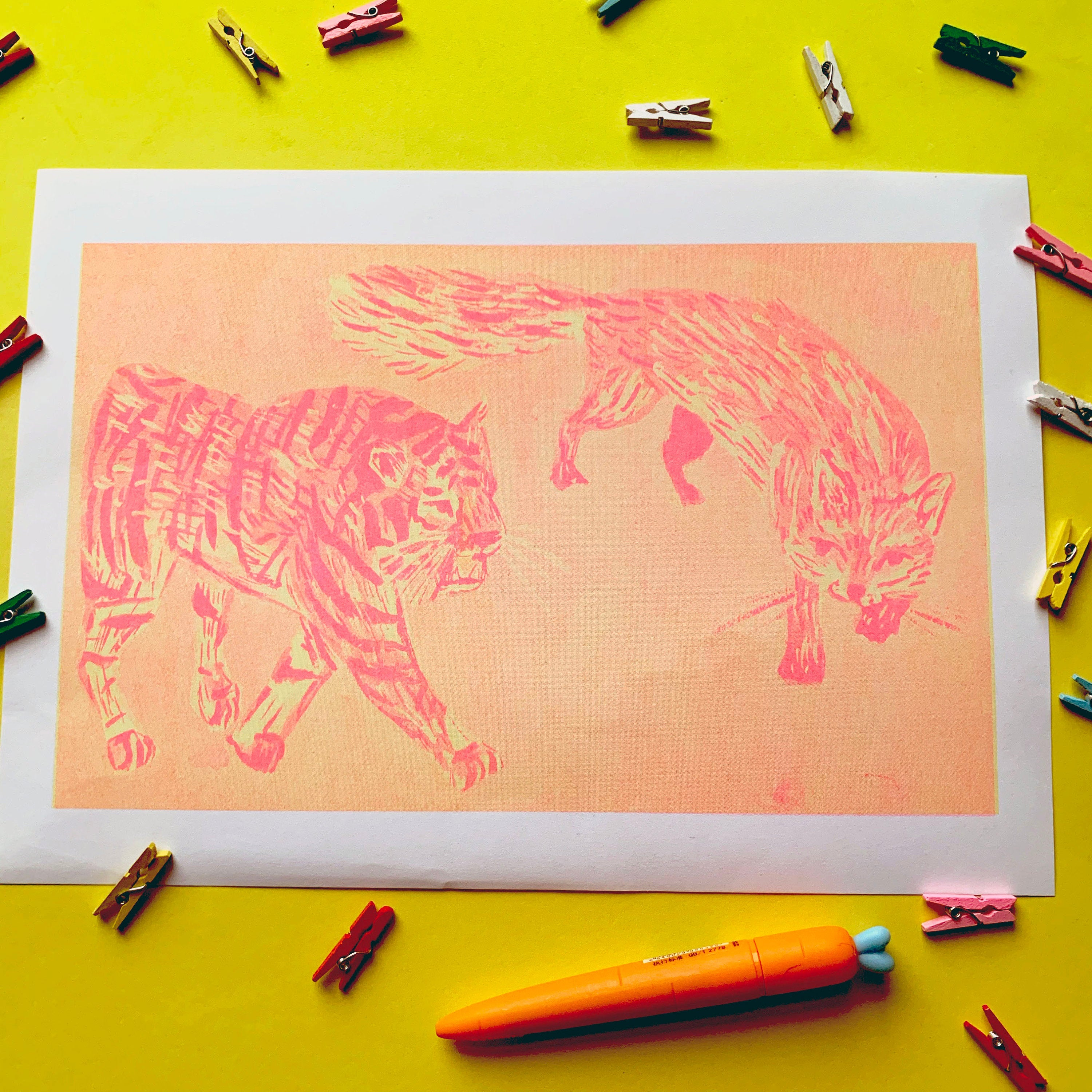 Image of an A4 risograph print. It depicts an illustration of a tiger and a fox. They were originally illustrated with gouache paint and then have been printed with a mixture of yellow and pink riso ink onto white recycled paper.