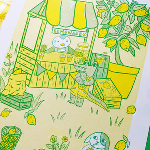 Image of an A4 risograph print against a yellow and green background. The print depicts a digital illustration of a lemonade stand scene. There is a penguin running a stall, a crocodile deciding what to order and a dog sat on a tree trunk enjoying his lemonade. There are details in the background such as a lemon tree and lemons scattered on the ground around little blades of grass. It has been printed with yellow and green riso ink on white recycled paper.