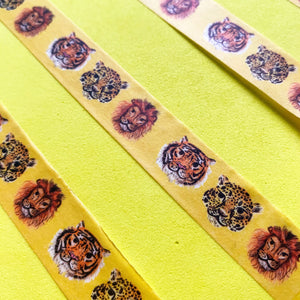 Roll of washi tape featuring an illustrated big cat design. If features a tiger, leopard and lion repeat pattern against a yellow background.