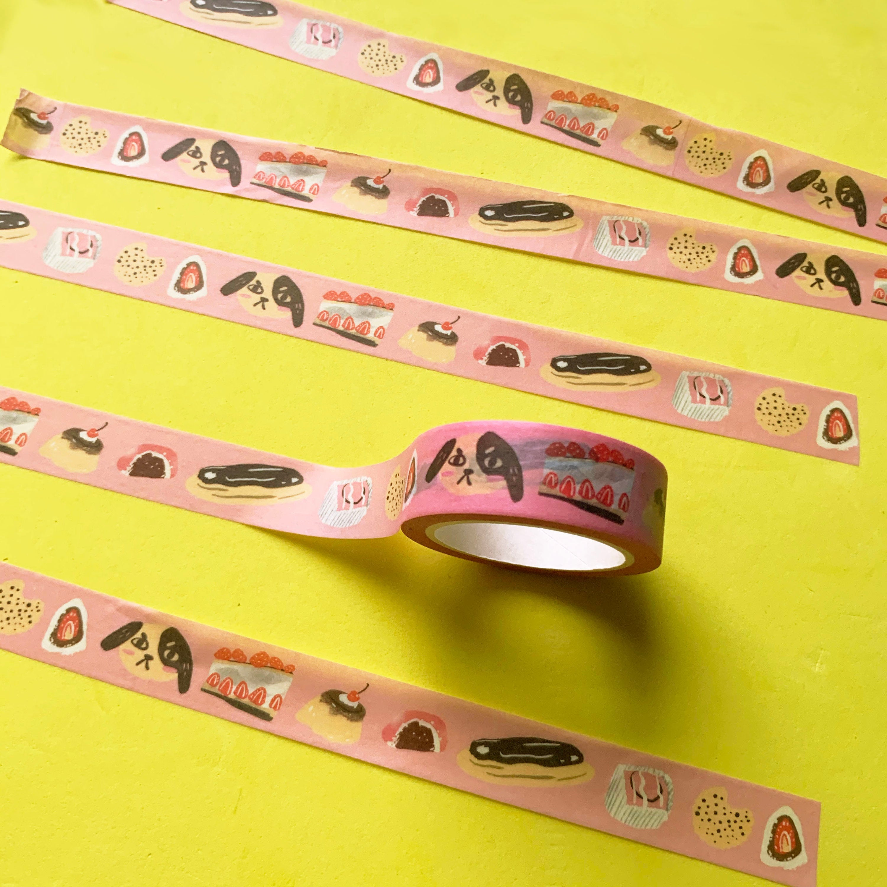 Image of a roll of paper washi tape against a yellow background. It depicts a cute dog with an angry face and a repeat pattern of desserts such as an eclair, cake, pudding, cookie, french fancy and mochi. It is printed onto a pink background.